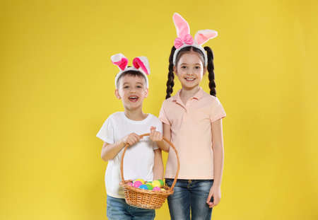 Cute children in bunny ears headbands holding basket with Easter eggs on color background