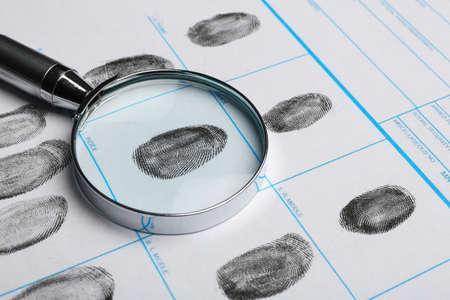 Magnifying glass and criminal fingerprint card, closeup