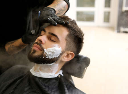 Professional hairdresser shaving client with straight razor in barbershop