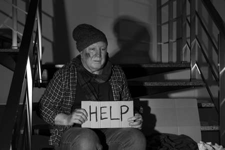 Poor senior man with cardboard sign HELP on stairs indoors. Black and white effect