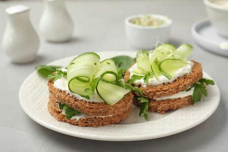 Placa con sándwiches de pepino tradicionales ingleses en mesa Foto de archivo