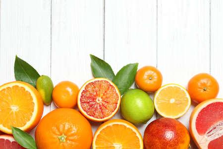 Platliggende compositie met verschillende citrusvruchten en ruimte voor tekst op witte houten achtergrond Stockfoto