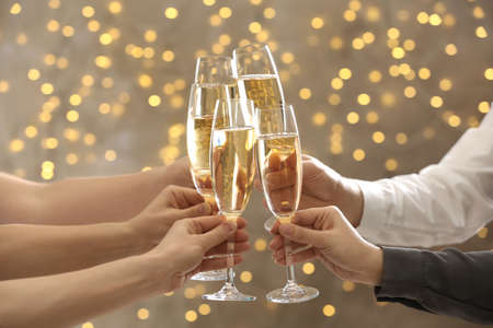 People clinking glasses of champagne on blurred background, closeup