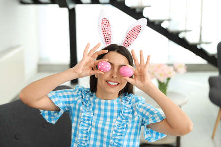 Beautiful woman in bunny ears headband holding Easter eggs near eyes at home