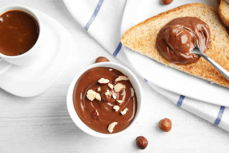 Sweet chocolate mousse served with coffee on wooden table, flat lay