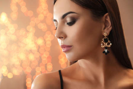 Beautiful young woman with elegant jewelry against defocused lights. Space for text