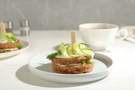 Plate with traditional English cucumber sandwich on table Foto de archivo