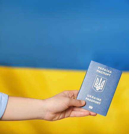 Woman with Ukrainian travel passport voting abroad, closeup. International relationships 写真素材
