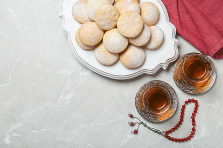 Flat lay composition with traditional Islamic cookies on table, space for text. Eid Mubarak