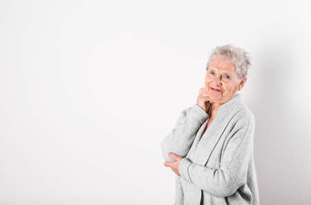 Portrait of grandmother in stylish clothes on light background, space for text