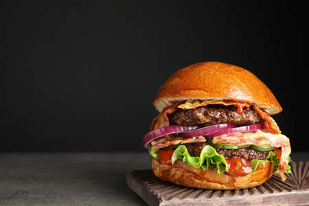 Tasty burger with bacon on table against black background. Space for text