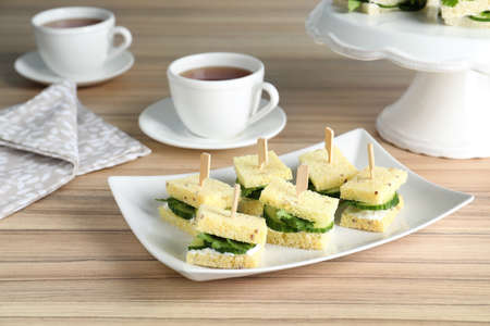 Plate with traditional English cucumber sandwiches on table Foto de archivo