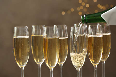 Pouring champagne into glasses on blurred background, closeup Imagens
