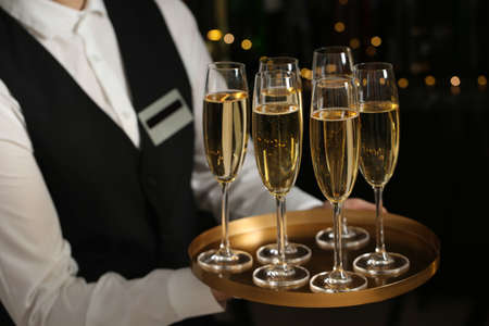 Waiter holding tray with glasses of champagne on blurred background, closeup Banco de Imagens