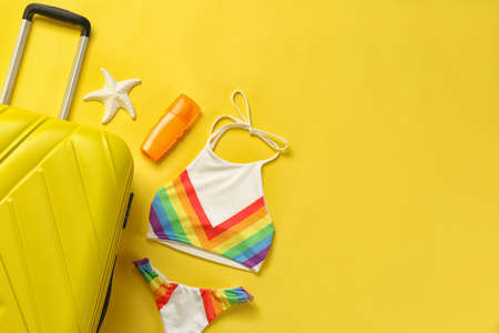 Flat lay composition with suitcase and  bikini on color background. Space for text