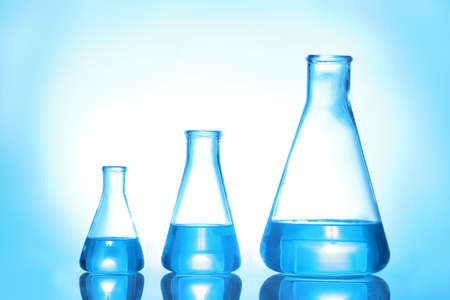 Laboratory glassware with liquid on color background. Solution chemistry Reklamní fotografie