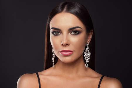 Mooie jonge vrouw met elegante sieraden op donkere achtergrond
