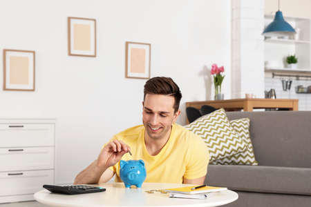 Happy man putting coin into piggy bank at table in living room. Saving money