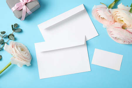 Flat lay composition with beautiful ranunculus flowers and envelopes on color background. Space for text Archivio Fotografico