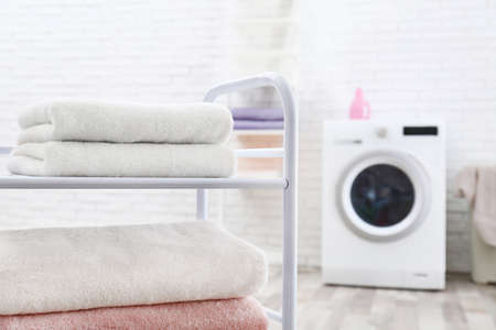 Folded clean terry towels on shelving unit in laundry room, space for text