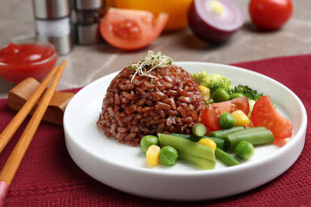 Plate of boiled brown rice with vegetables served on table