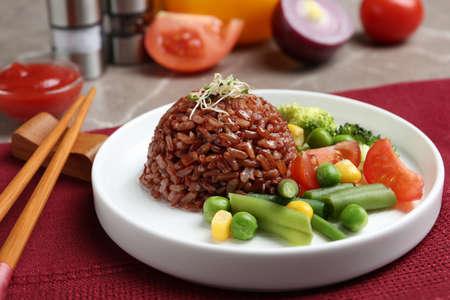 Teller mit gekochtem braunem Reis mit Gemüse auf dem Tisch serviert