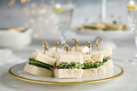 Plate with traditional English cucumber sandwiches on table. Space for text