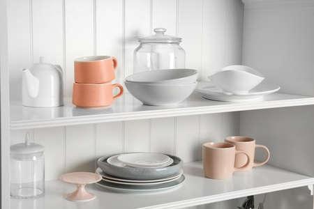 Soporte de almacenamiento elegante con diferentes vajillas de cerámica en casa