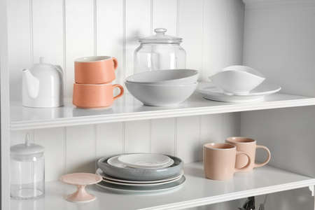 Stylish storage stand with different ceramic dishware at home