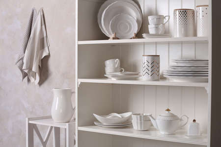 Stylish storage stand with different ceramic dishware at home 写真素材