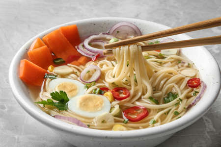 Eating noodle dish with chopsticks on table, closeup