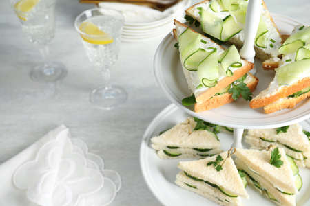 Stand with traditional English cucumber sandwiches on table. Space for text