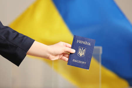 Woman holding Ukrainian internal passport against national flag at polling station, closeup