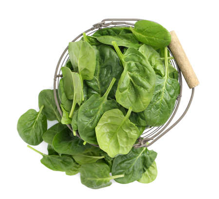 Basket and spinach leaves isolated on white, top view