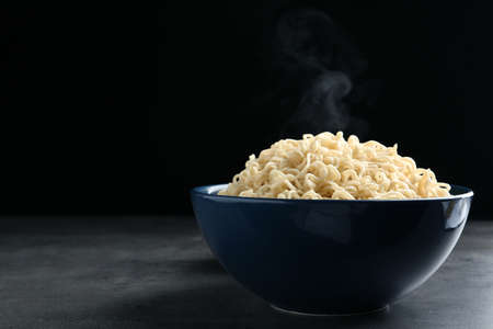 Bowl of hot noodles on table against black background. Space for text