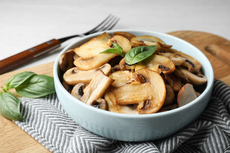 Delicious cooked mushrooms with basil served on table