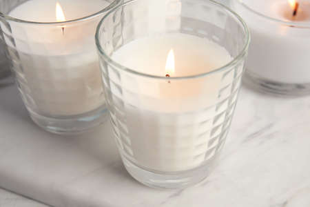 Burning candles in glass holders on table, closeup