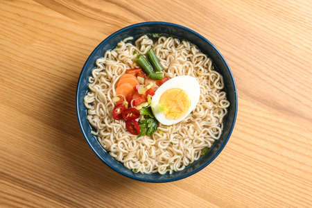 Bowl of noodles with broth, egg and vegetables on wooden background, top view Reklamní fotografie