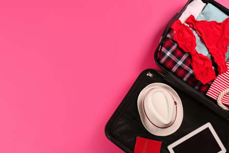 Open suitcase with traveler's belongings on color background, top view. Space for text