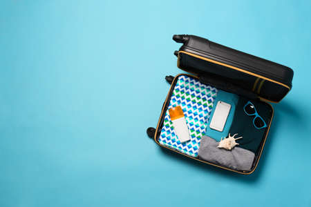 Open suitcase with travelers belongings on color background, top view. Space for text 版權商用圖片