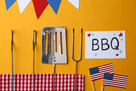 Flat lay composition with barbecue tools and card on color background. USA Independence Day