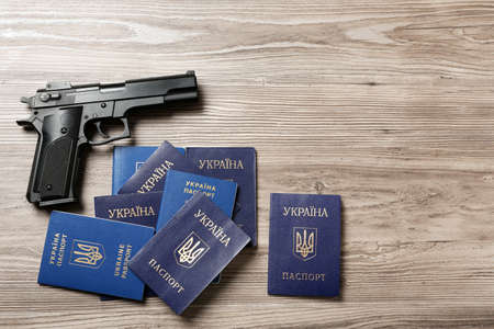 Gun with Ukrainian passports on wooden background, flat lay. Space for text 写真素材