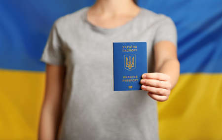 Woman holding Ukrainian travel passport against national flag, closeup with space for text. International relationships