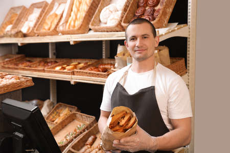 Professional baker holding paper bag with pastry in store 版權商用圖片