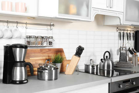 Different appliances, clean dishes and utensils on kitchen counter