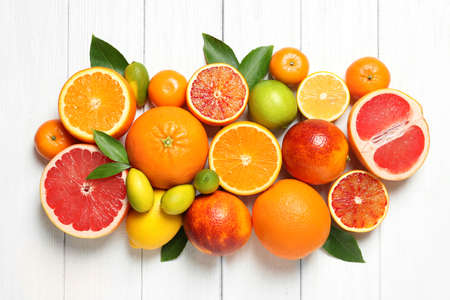 Flat lay composition with different citrus fruits on white wooden background