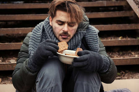 Poor young man with bread sitting on stairs outdoors