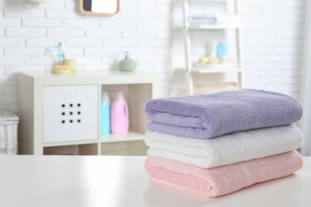 Stack of fresh towels on table in bathroom. Space for text