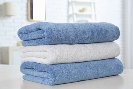 Stack of fresh towels on table in bathroom, closeup