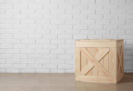 Wooden crate on floor near brick wall, space for text